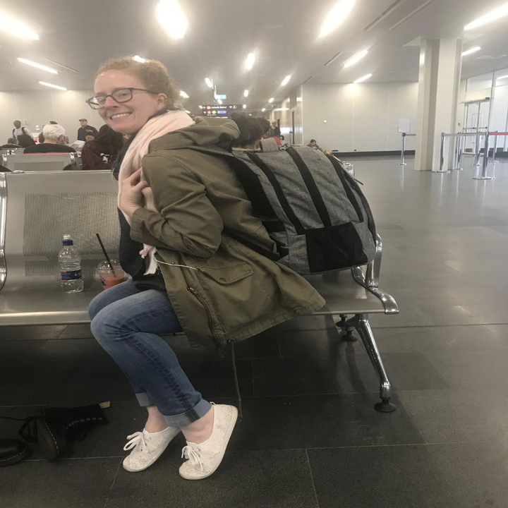 Reviewer wearing gray backpack full of items