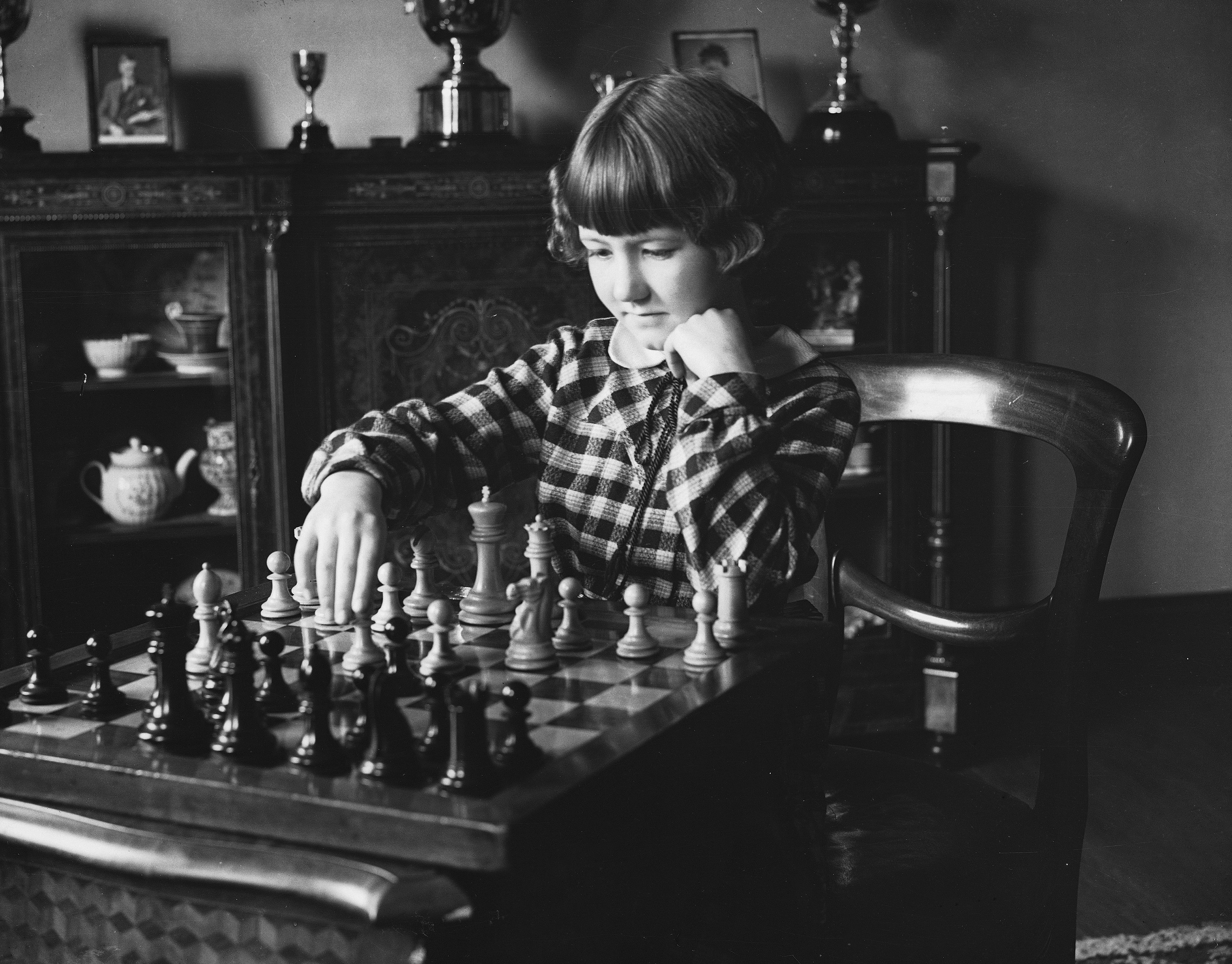 A young girl in a checkered dress plays chess in front of trophies on a shelf