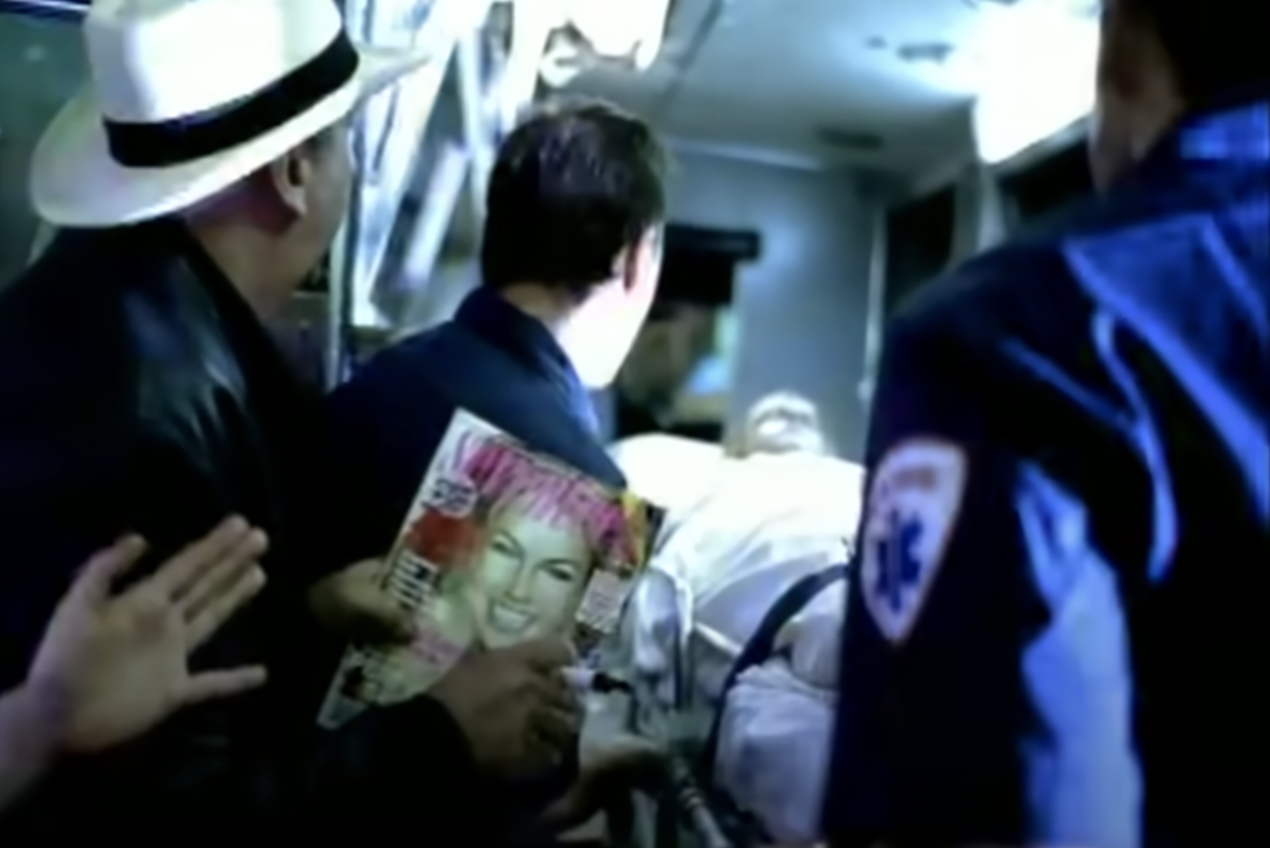 Britney being carried away in a stretcher while paparazzi watches
