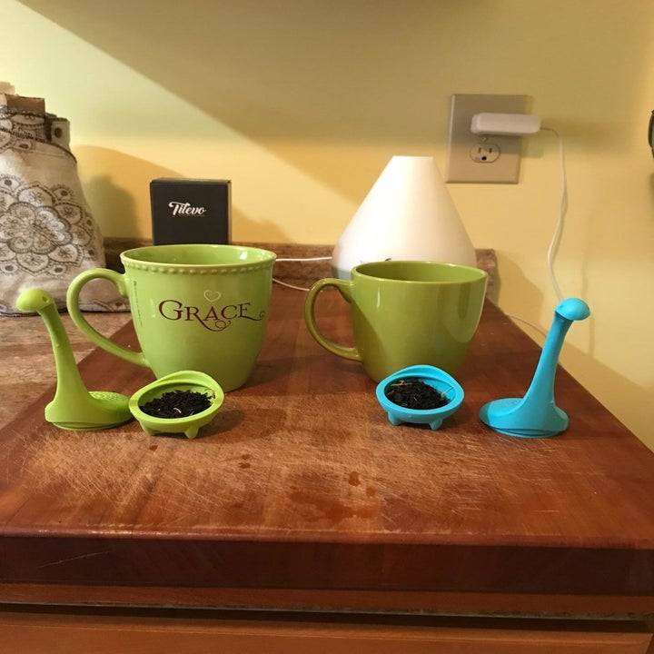 reviewer image of the pair of tilevo dinosaur tea infusers opened to reveal tea leaves