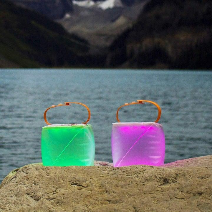 Two lanterns emitting green and purple light