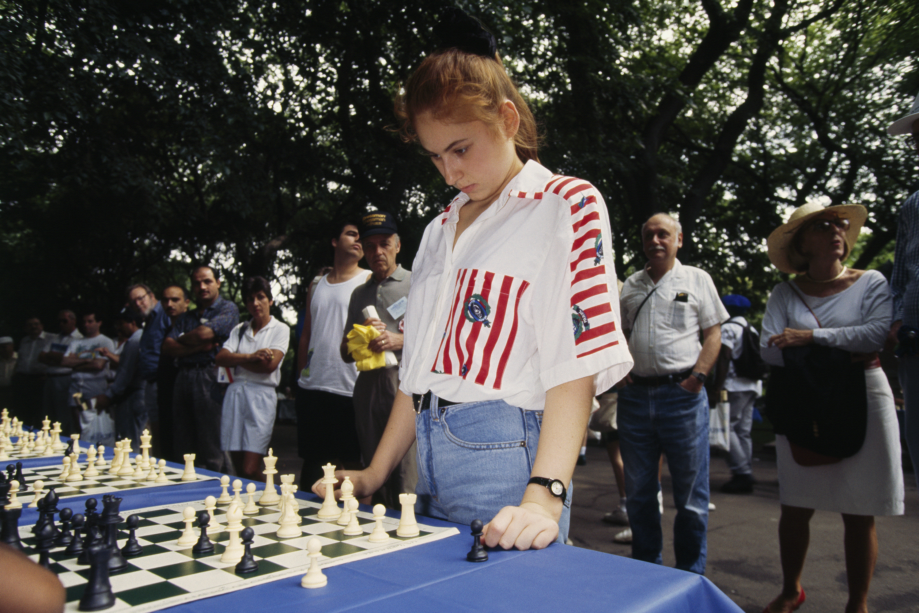 A redheaded girl stares intently at a chessboard while a crowd watches behind her