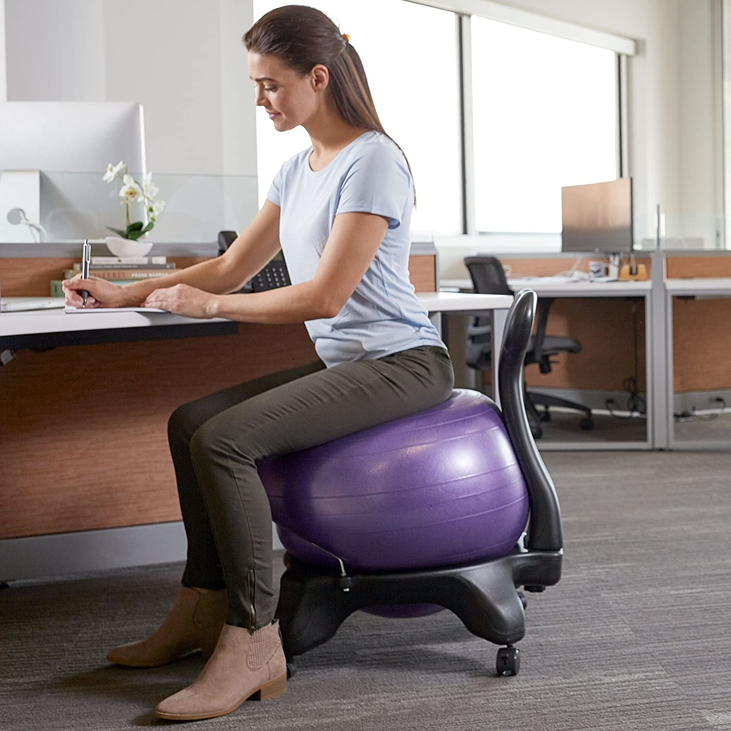 Model sitting on an office chair with a purple blow up ball on it