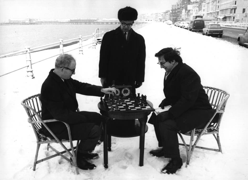 Two men seated in the snow play chess as one man, standing and wearing an ushanka, watches them play
