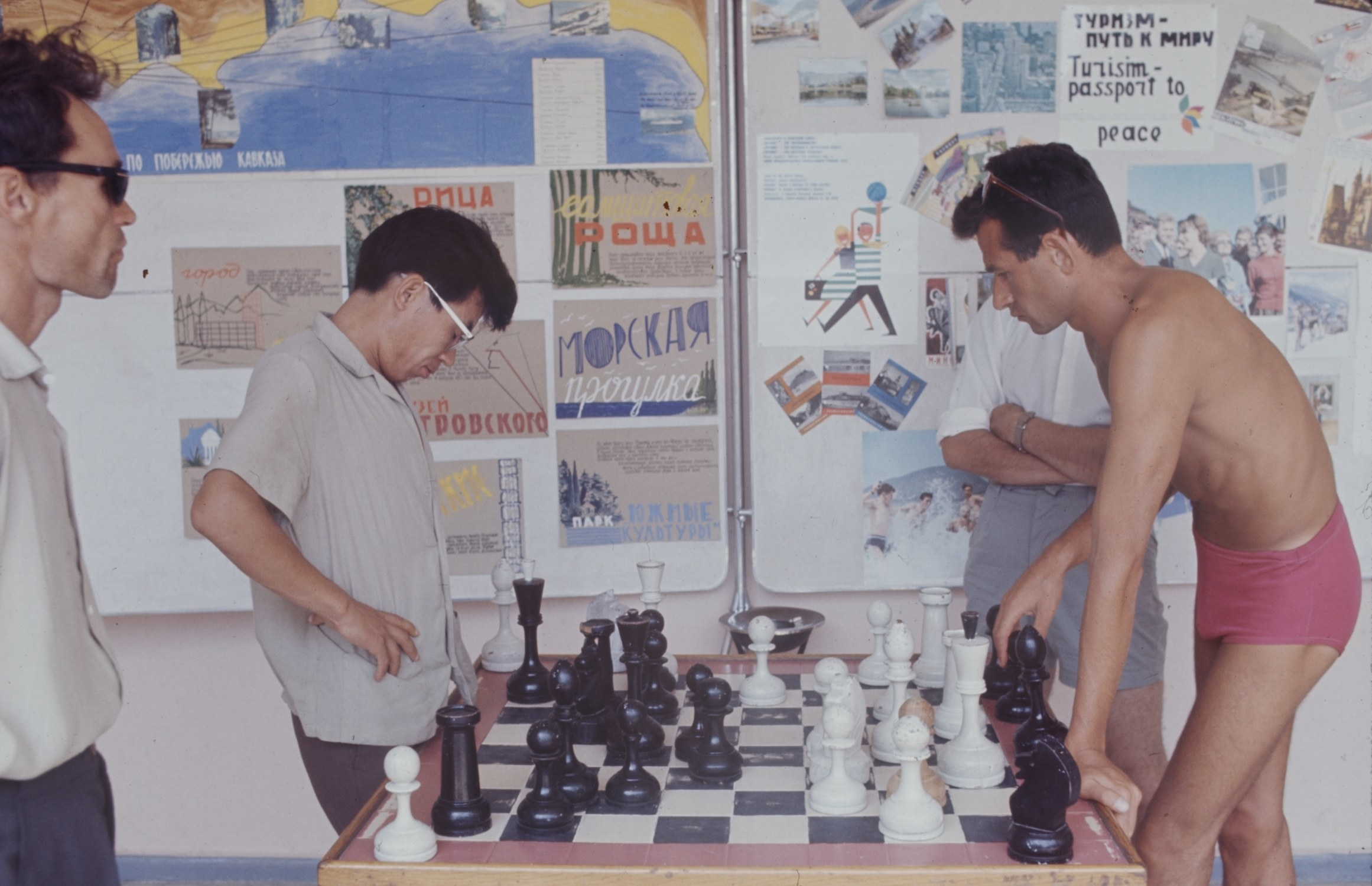 A man in a polo shirt plays large-scale chess with a man in pink bathing shorts