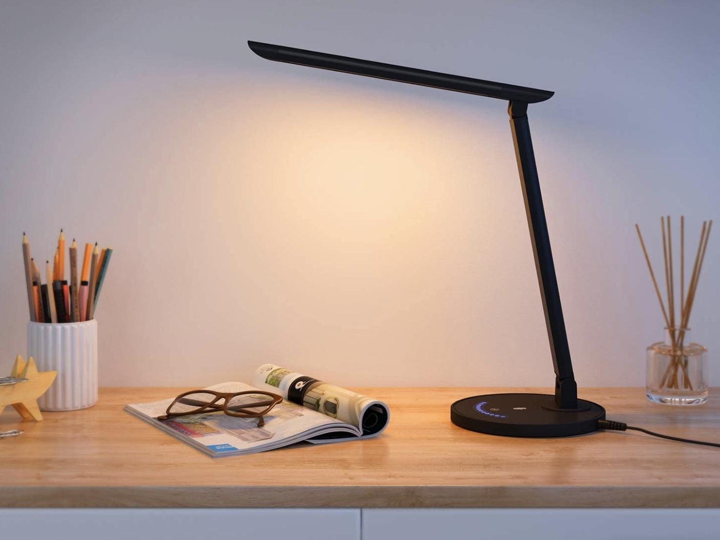 A black L-shaped desk lamp perched on a desk