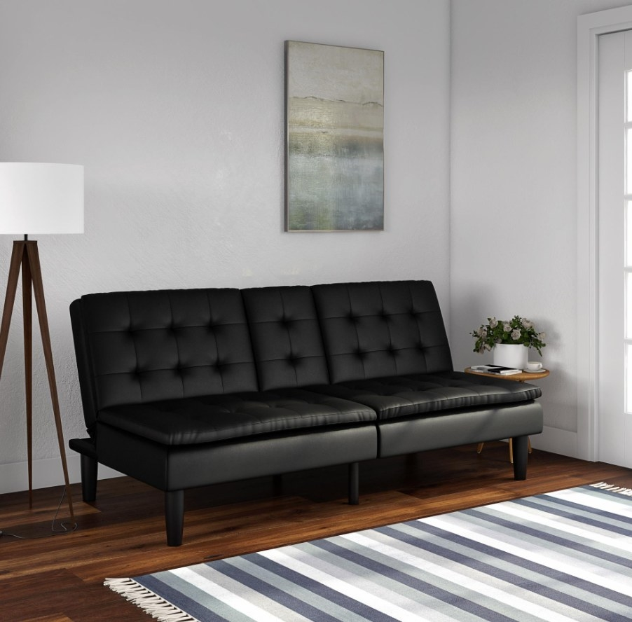 The futon in the color black faux leather