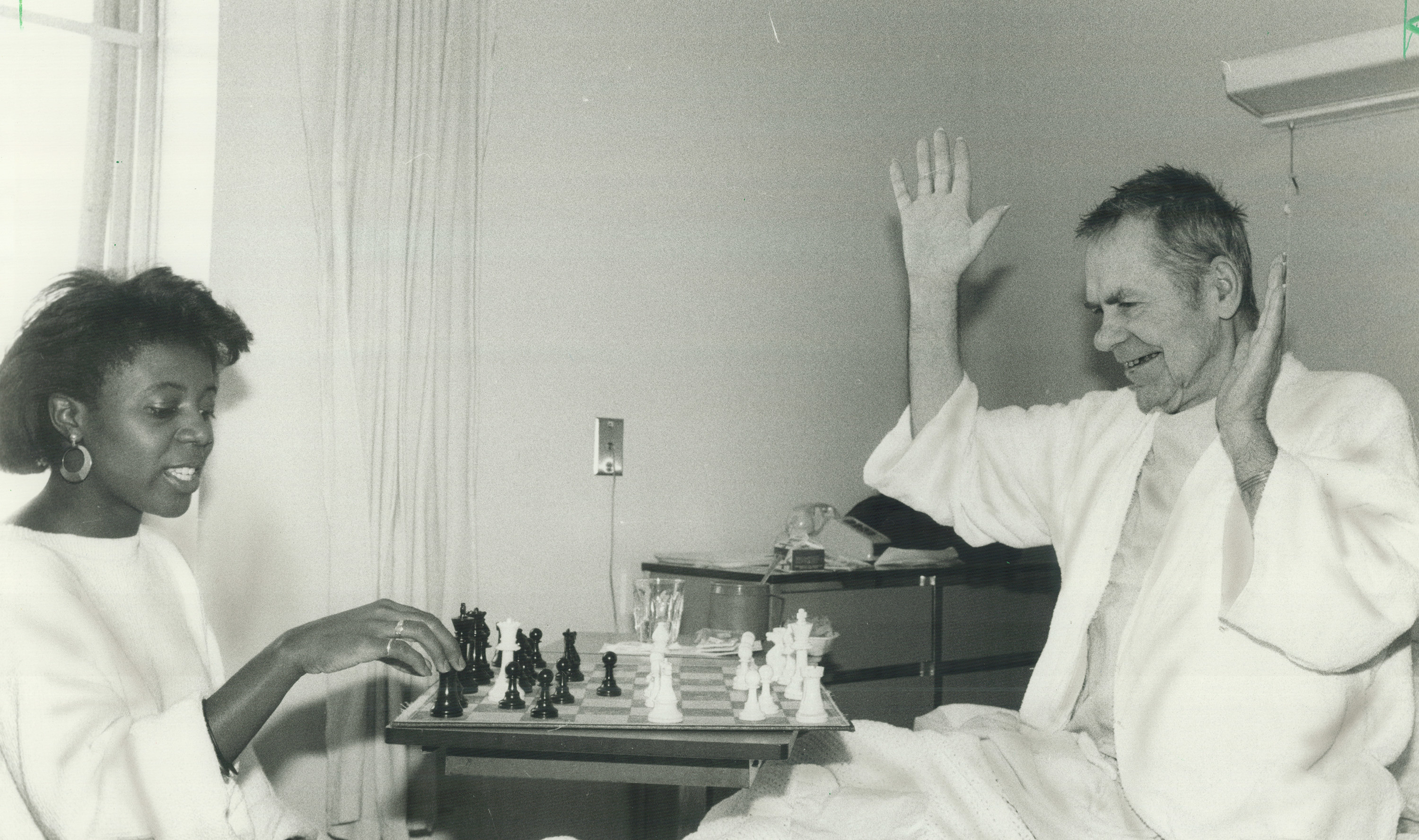 A young woman and an old man in a hospital bed playing chess.