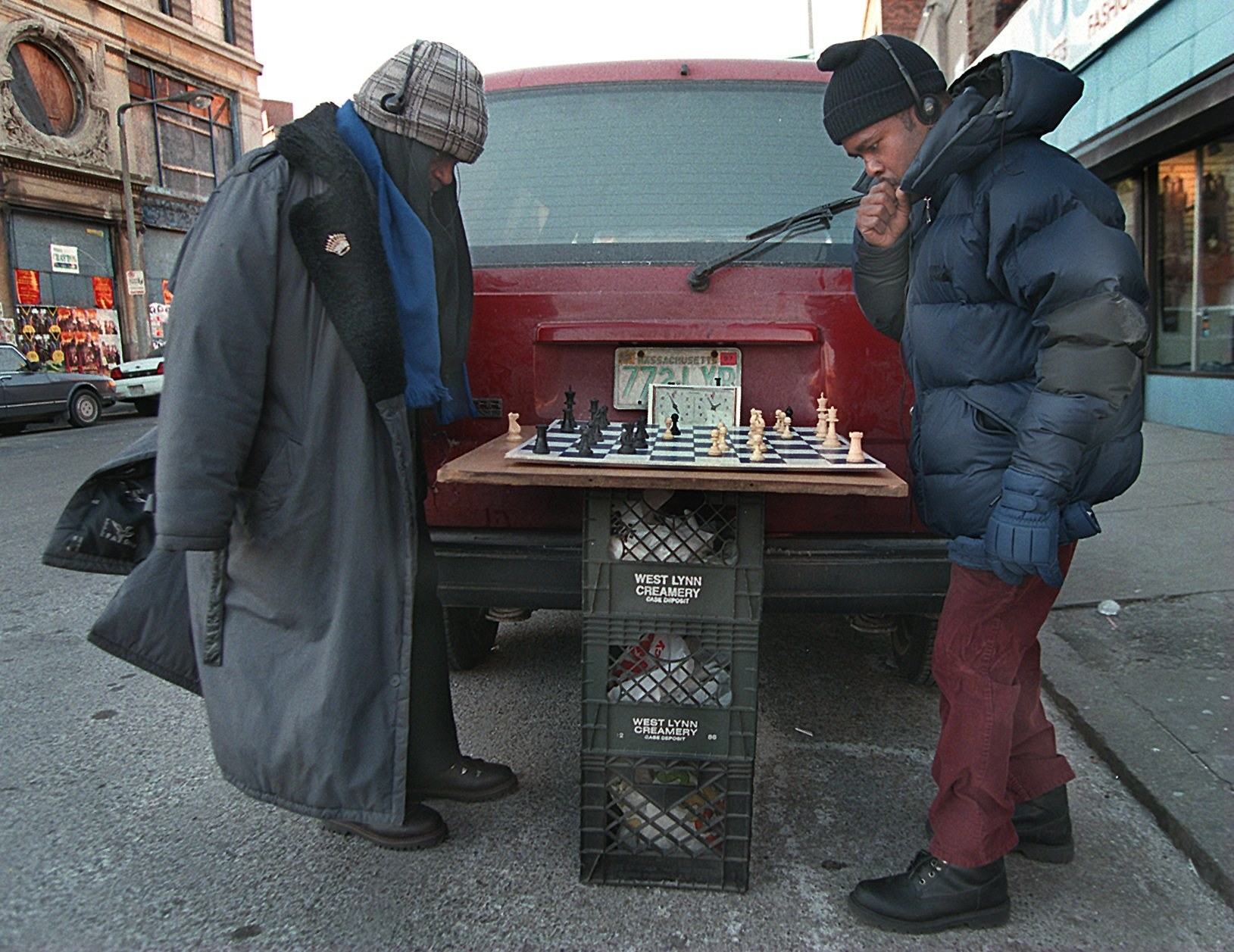 Two Black men in overcoats and hats play chess on three stacked-up milk crates behind a maroon minivan
