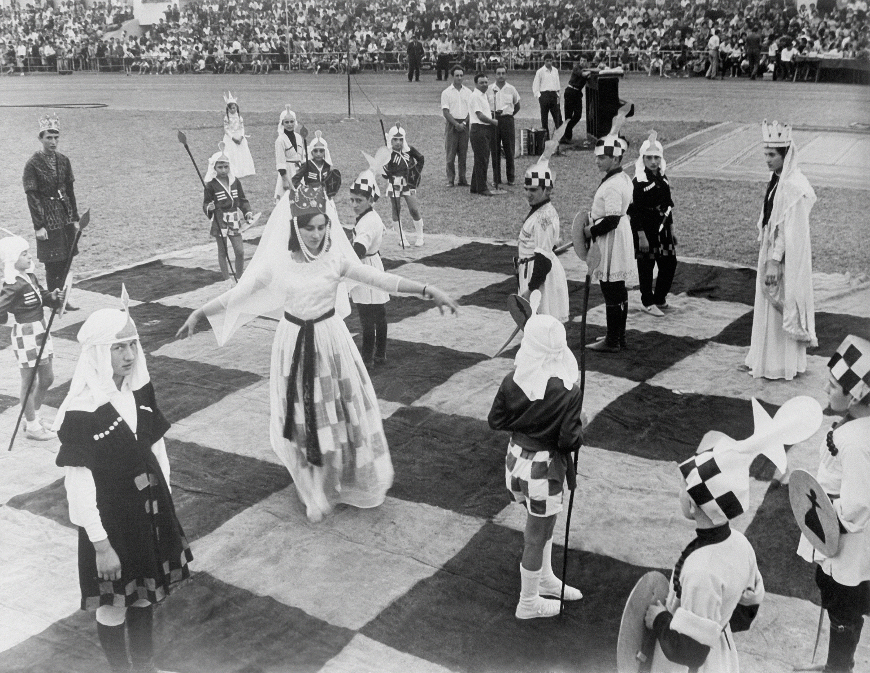 A woman dressed as a chess queen, with a crown and checkerboard dress, has her arms outstretched, standing on a giant chessboard and surrounded by other people dressed as pieces