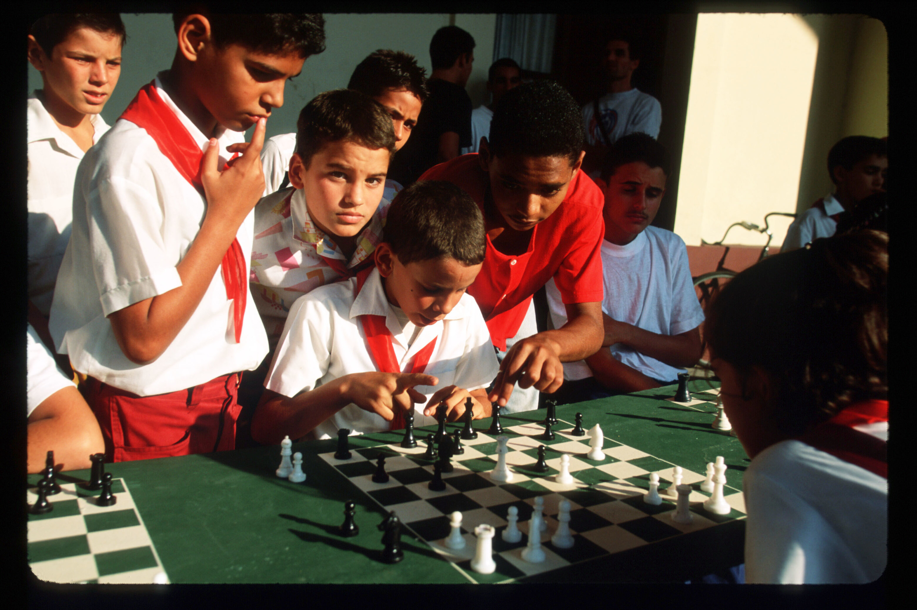 Boys in red-and-white uniforms huddle around a green-and-white chessboard