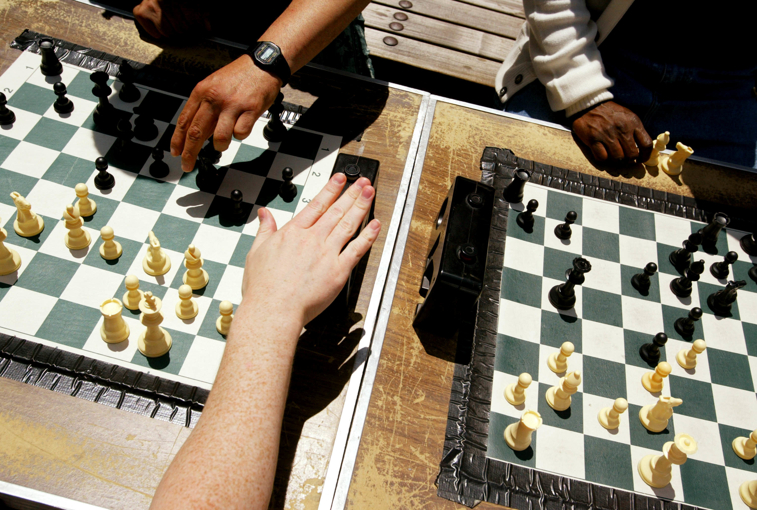 A hand depresses a chess clock on a table between two chessboards in the sunlight.