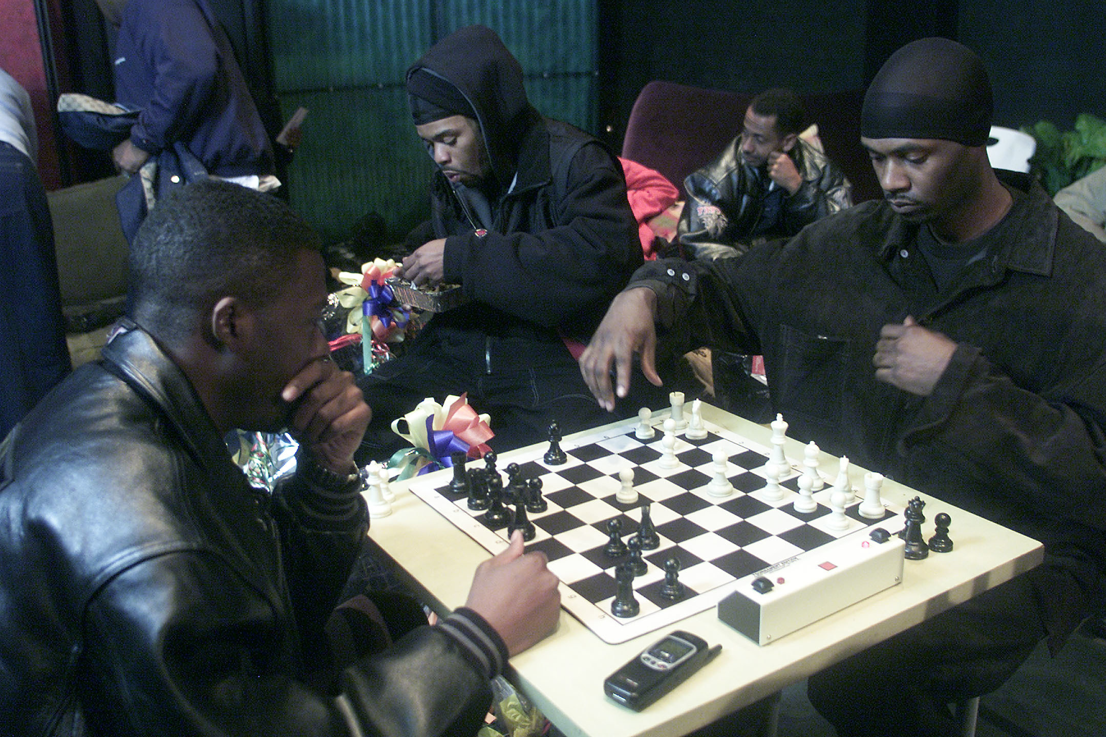Four men hang out in a backstage green room; two of them in the foreground play chess