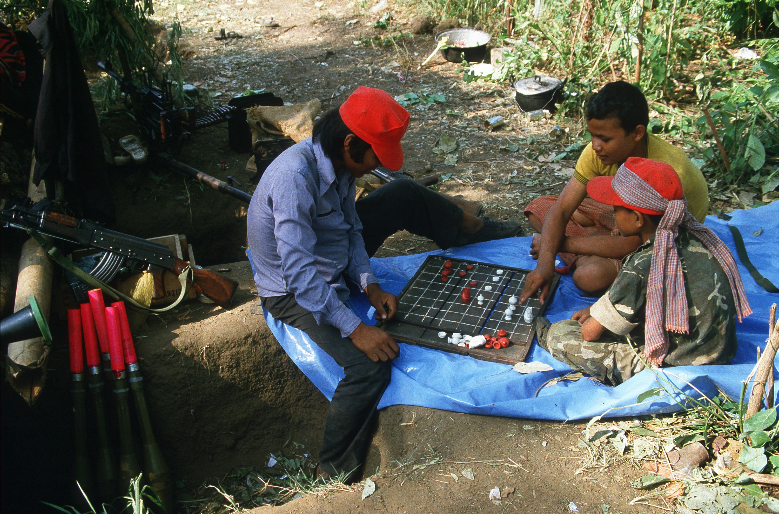Three child soldiers play chess on a blue tarp outside