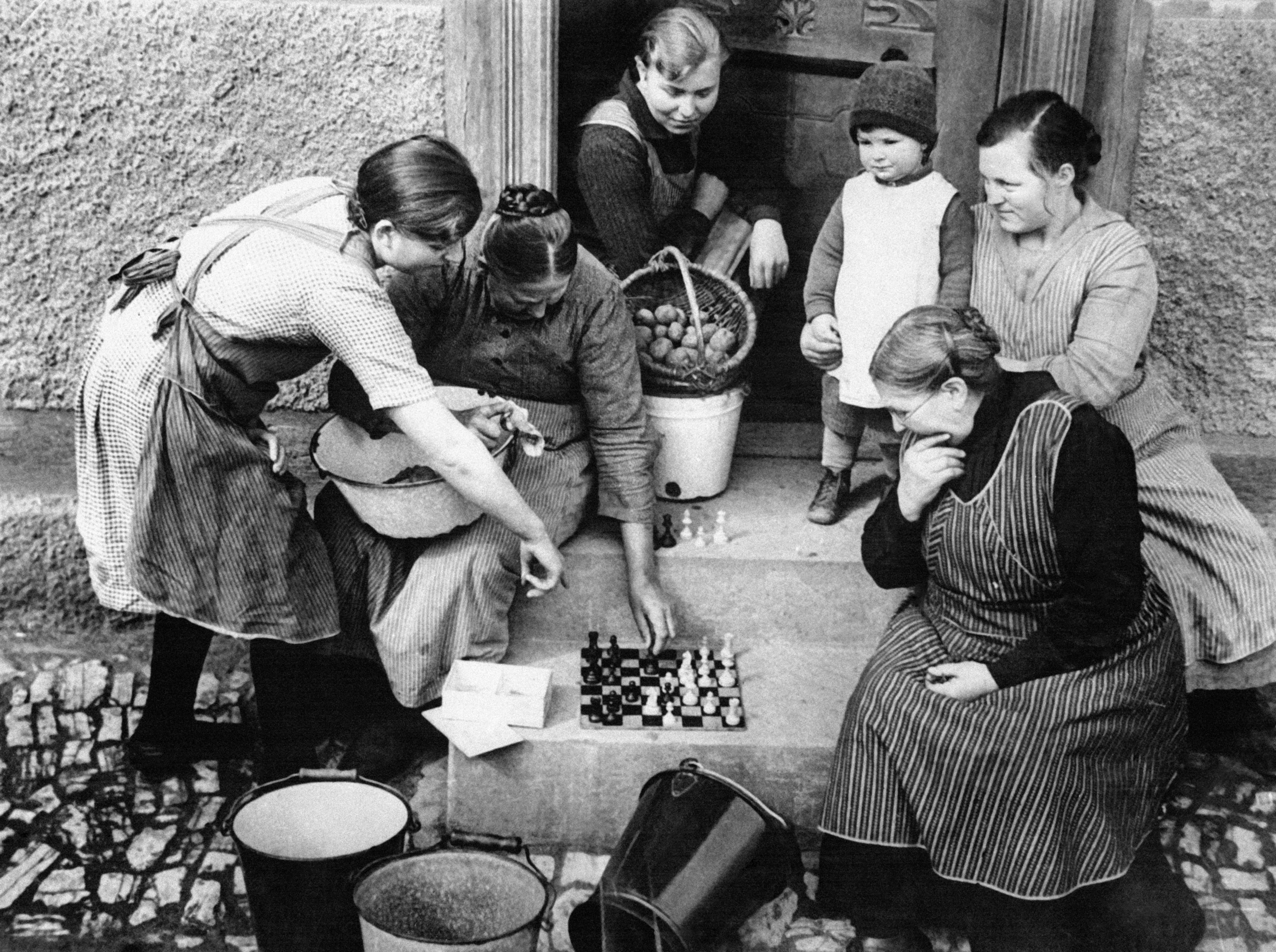 Five women and a toddler, all in aprons and old-fashioned clothing, huddle around a chessboard on a stoop