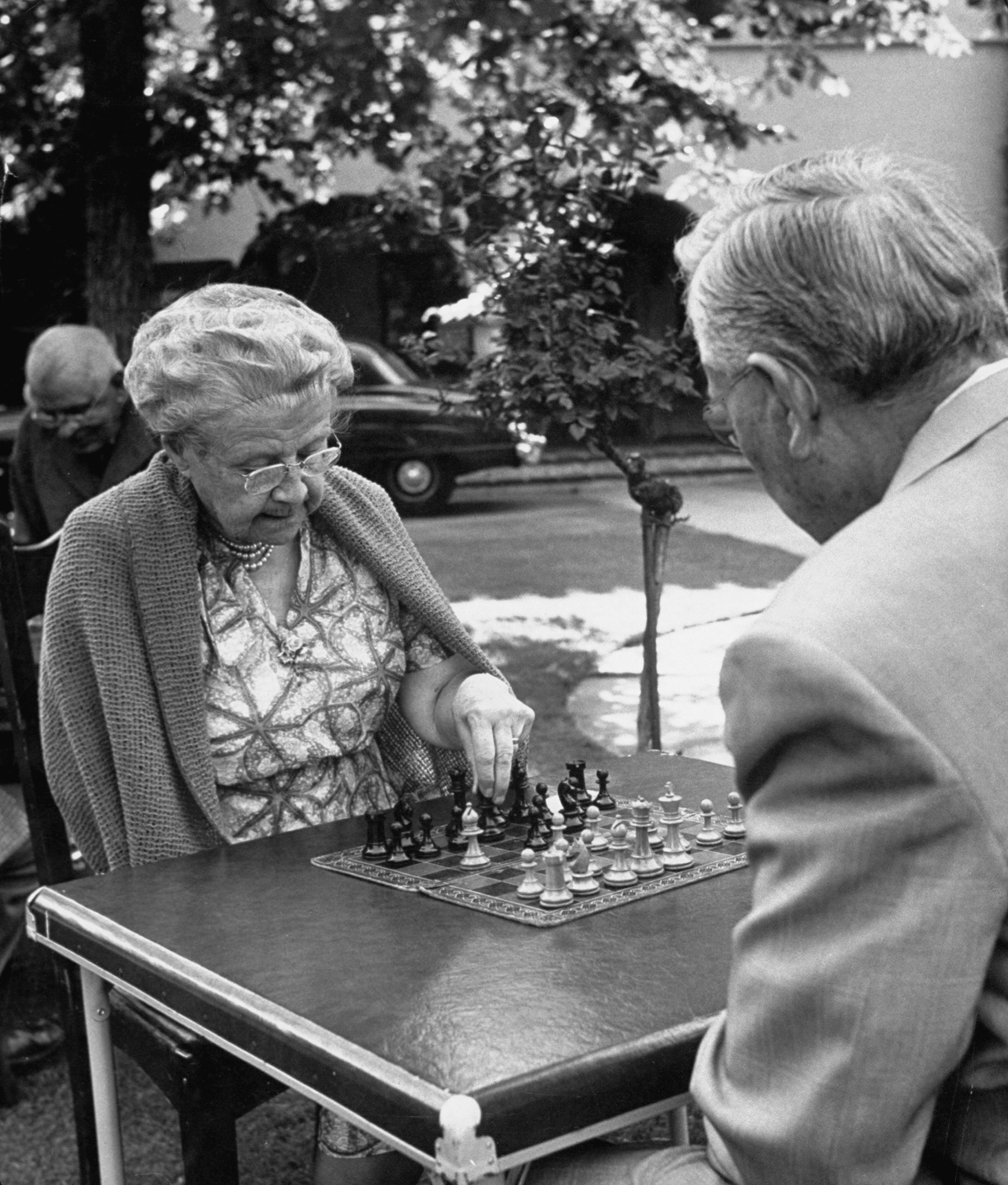 An older woman and an older man play chess outside on a sunny day