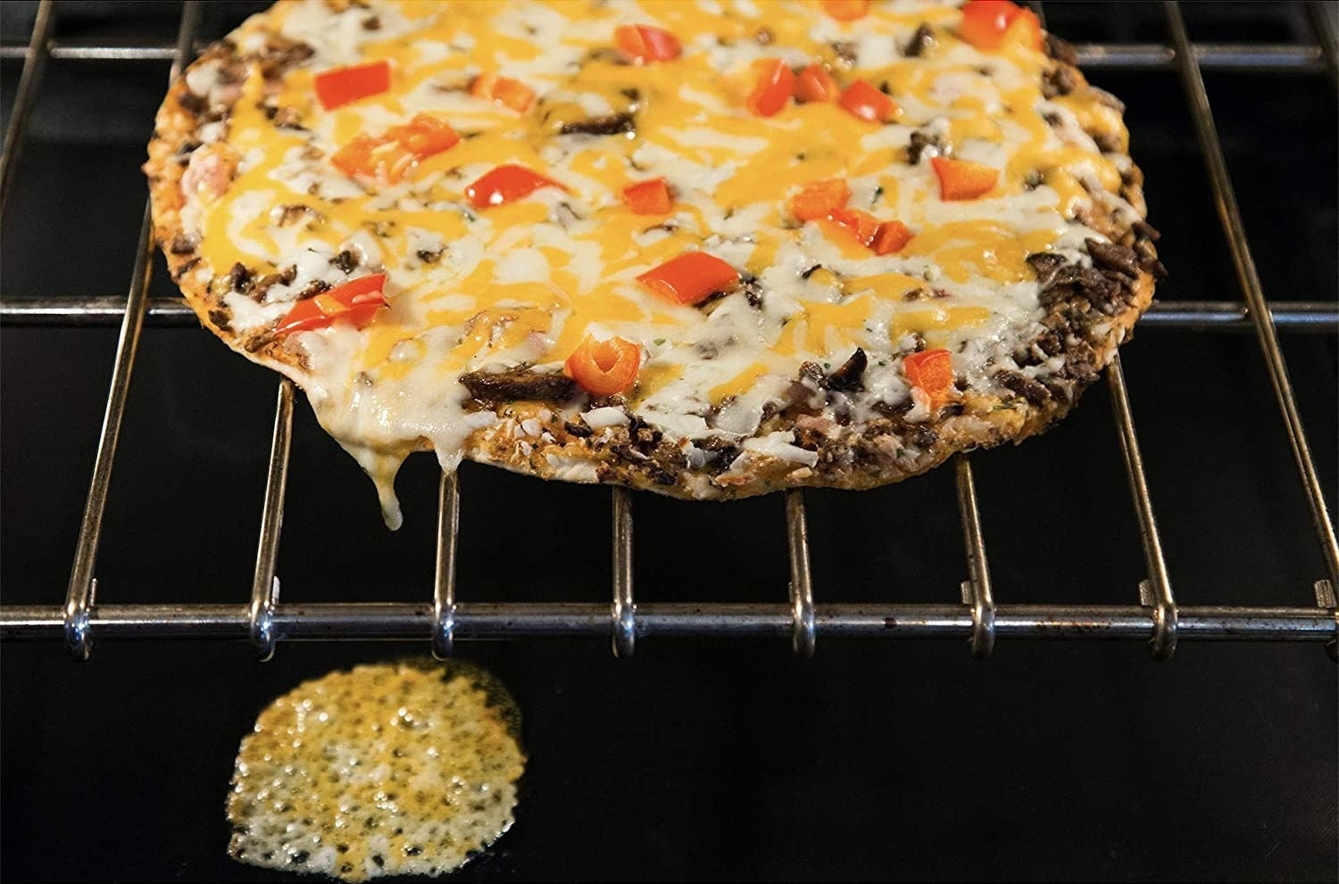 pizza in the oven with cheese dripped onto oven mat