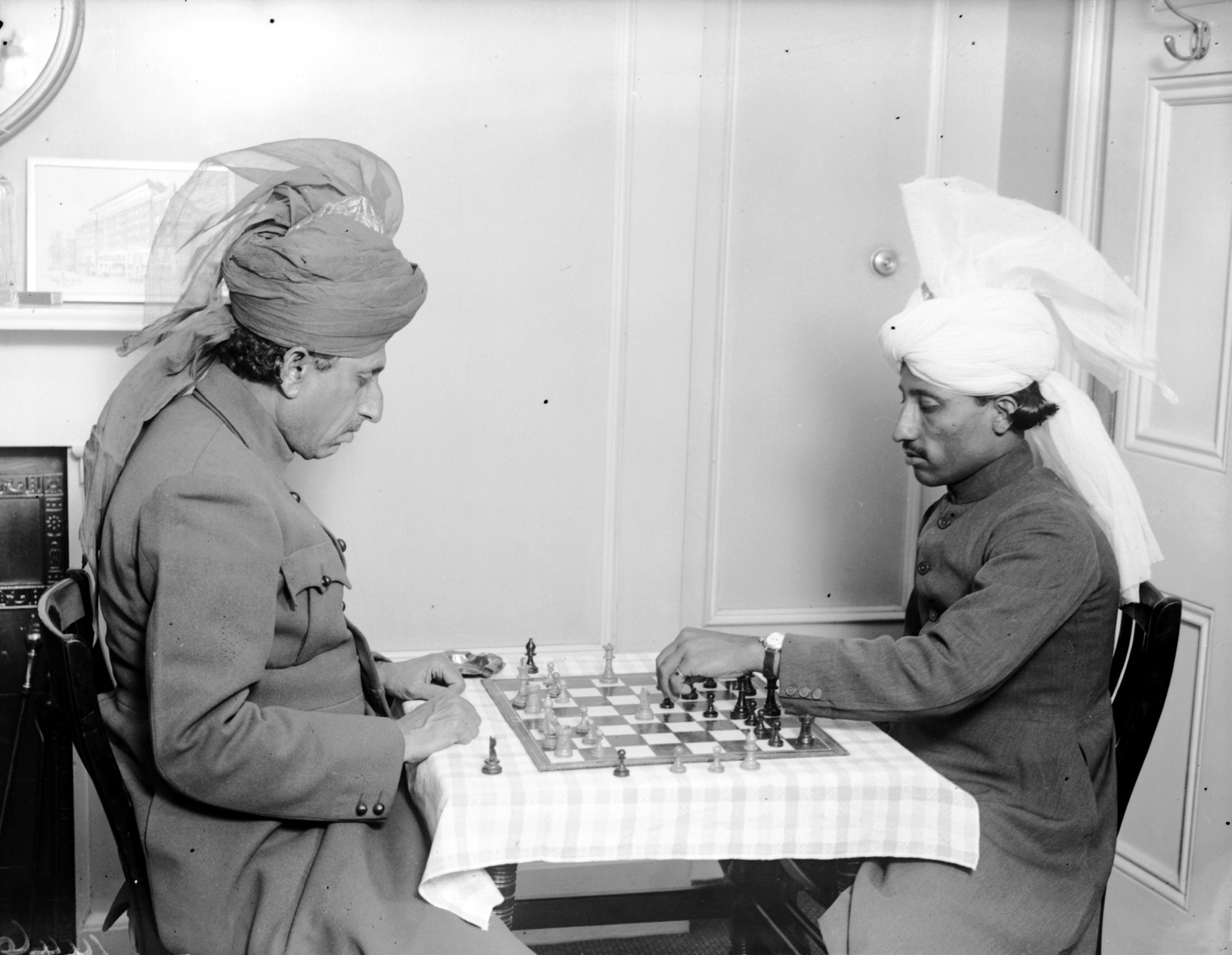 Two men in uniforms and turbans playing chess indoors