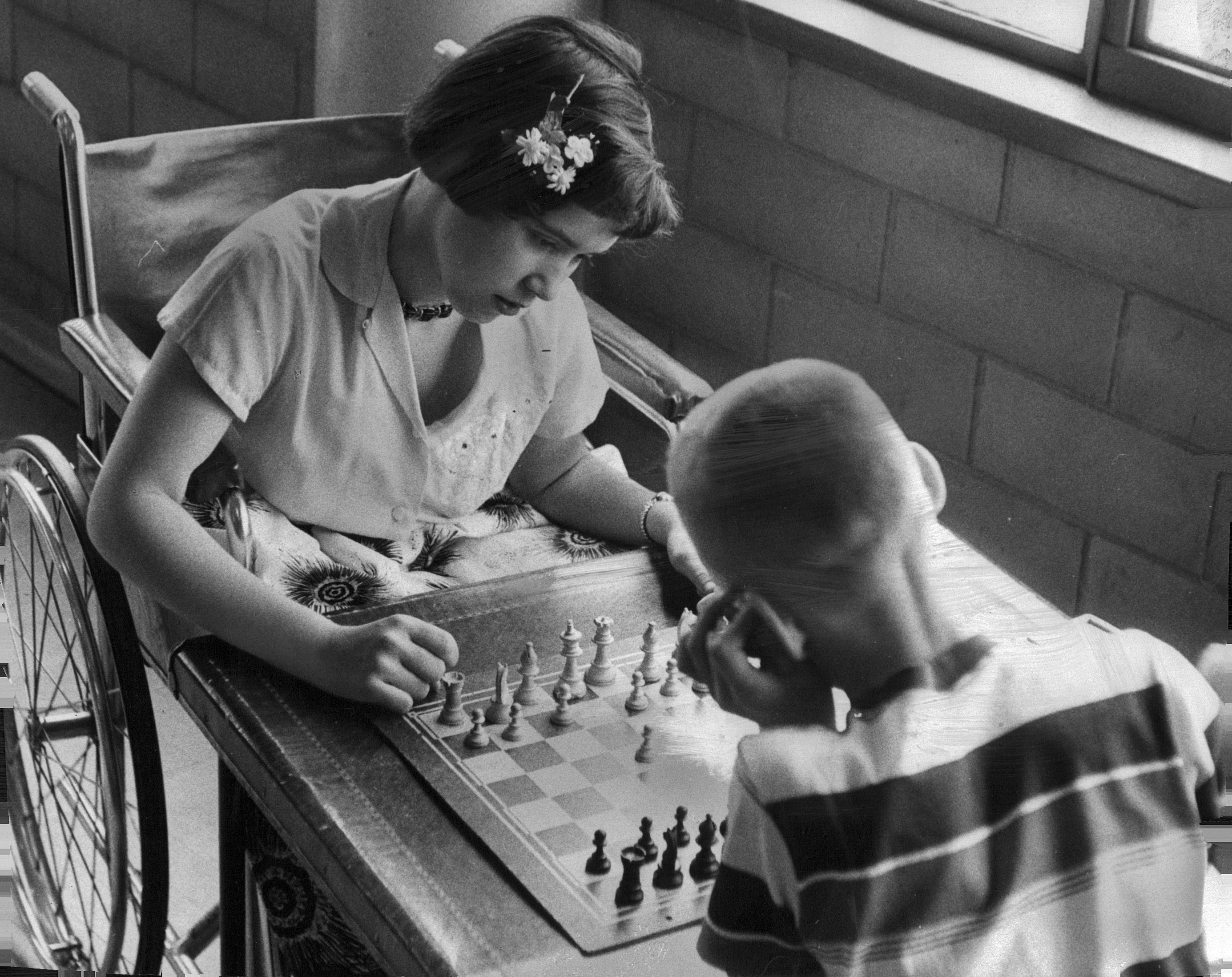 A girl in a wheelchair plays chess with a young boy