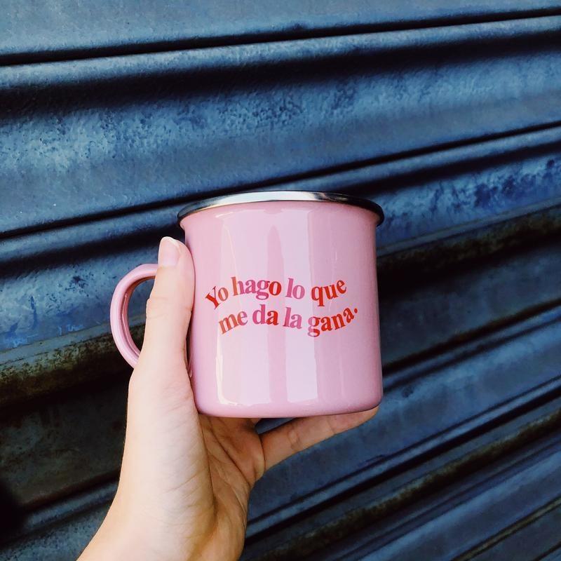 """A pink enamel mug that says """"yo hago lo que me de la gana"""""""