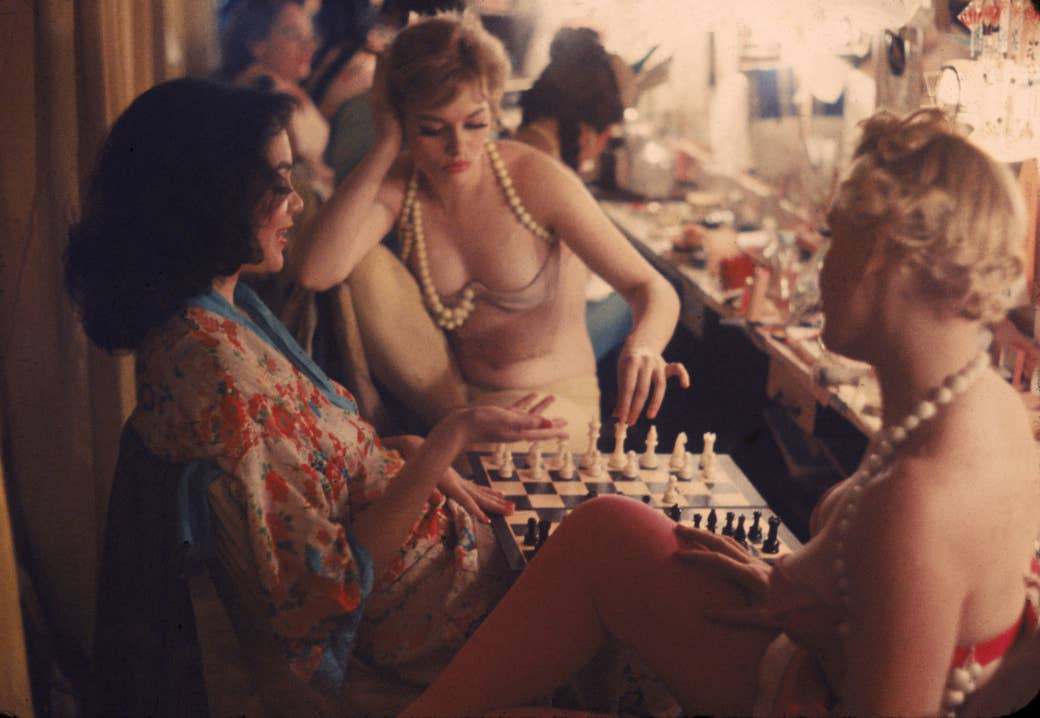 Three women in a backstage green room, wearing robes, underwear, and pearls, sit around a chessboard
