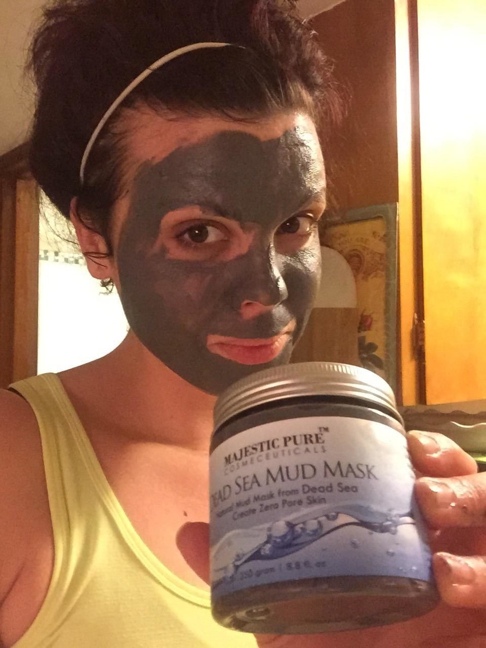 Reviewer wears dark gray dead sea mud mask on their face