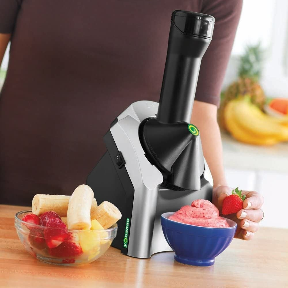 Model placing strawberry on top of bowl of soft serve under Yonanas machine