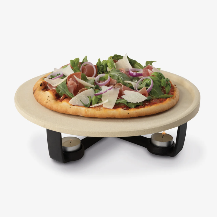 Pizza on top of pizza stone with candle tea lights underneath
