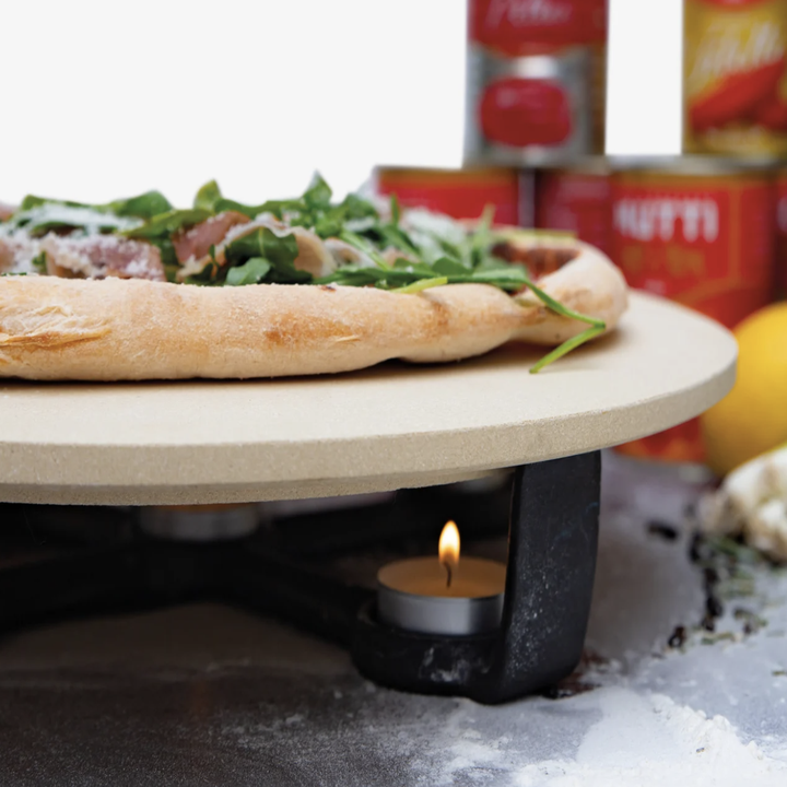 Closeup shot of candle tea light underneath pizza stone