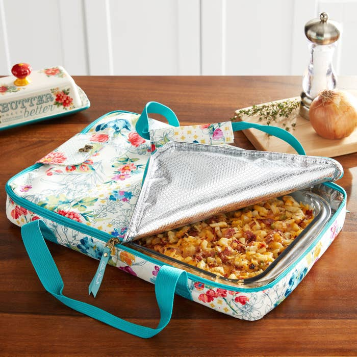 The Pioneer Woman Blooming Bouquet Foldable Tote, on a table, shown unzipped and with a casserole inside.