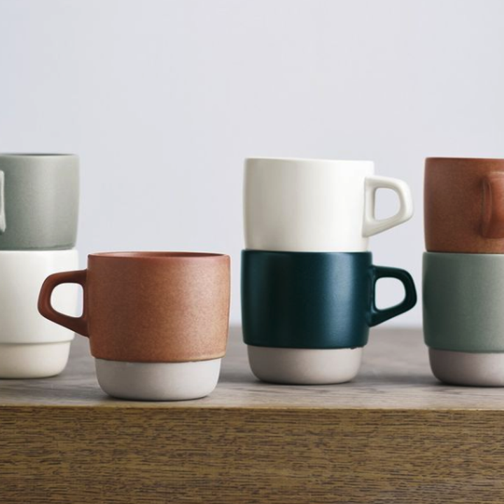 A bunch of earth-toned mugs on a white marble countertop