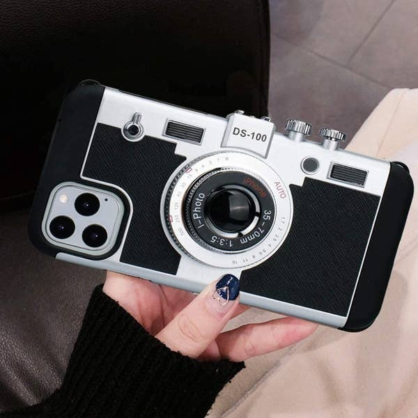 An iPhone case designed to look like a vintage camera with a camera lens and buttons