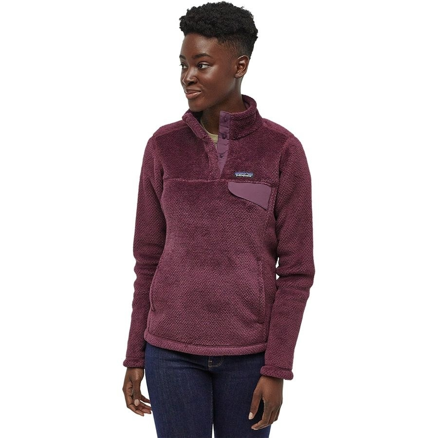 a model in a purple fleece jacket with buttons half way from the top