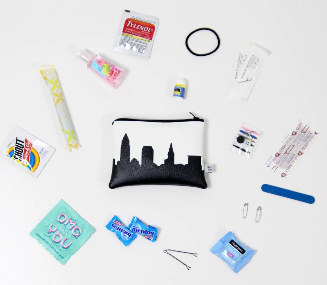 A small white faux leather pouch with a black skyline print surrounded by a mix of travel-sized toiletries and on-the-go essentials