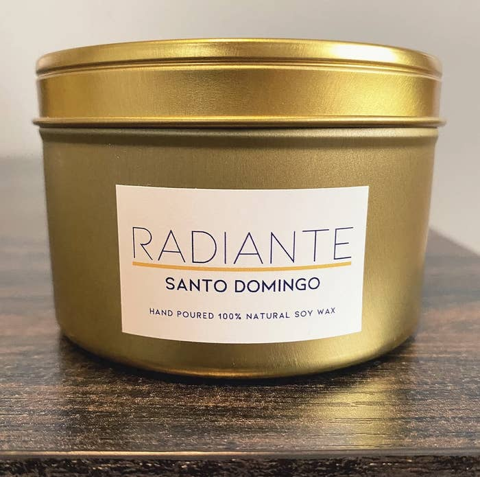 A gold candle that says Radiante and Santo Domingo on it