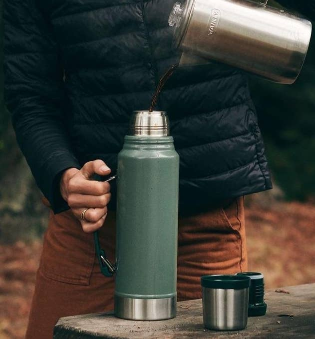 A person pouring coffee from a kettle into a vacuum insulated thermos