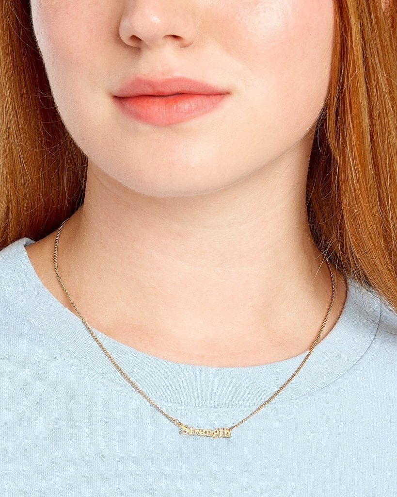 """a model wearing the necklace that reads """"strength"""" on a gold chain"""