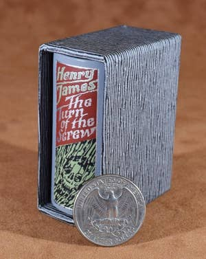 A miniature book that says The Turn of the Screw that's about the size of 3 quarters