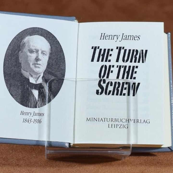 That same miniature book open showing the first page and a portrait of the author