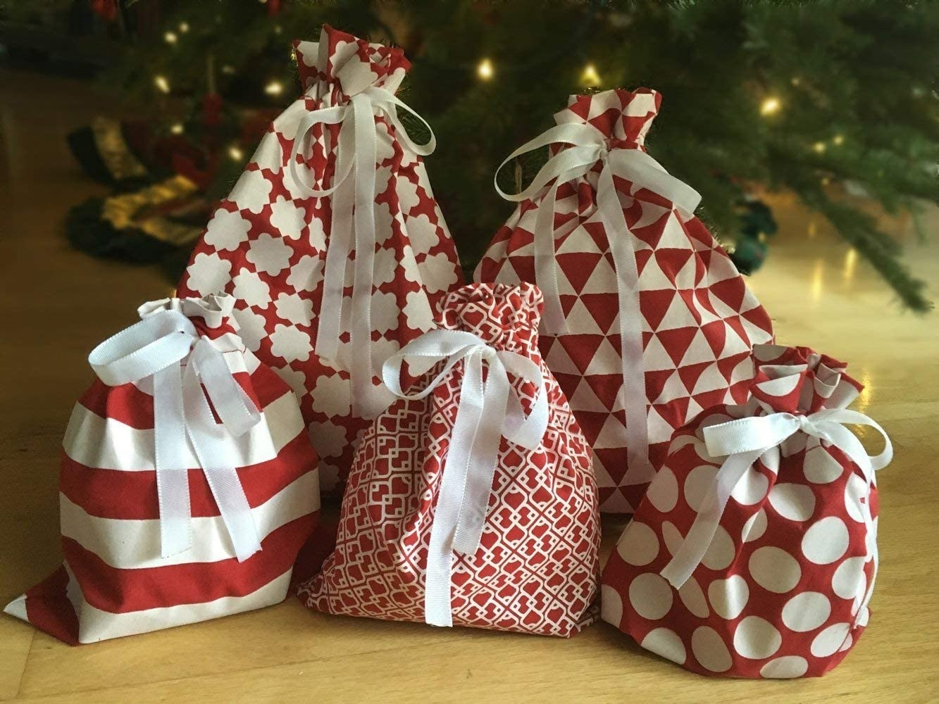five gift sacks of various red and white patterns