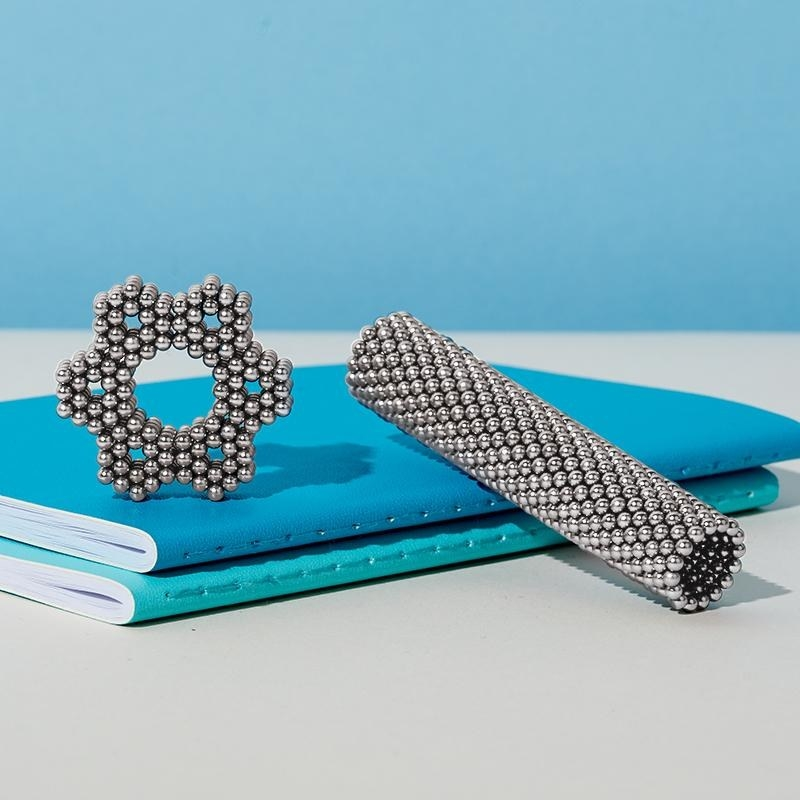 two speks magnetic balls shaped into a hexagon and cylinder, respectively