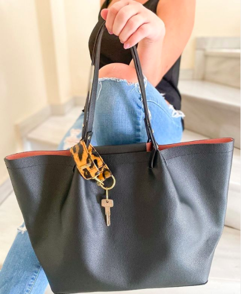 person holding up tote purse with a loop keychain around a handle