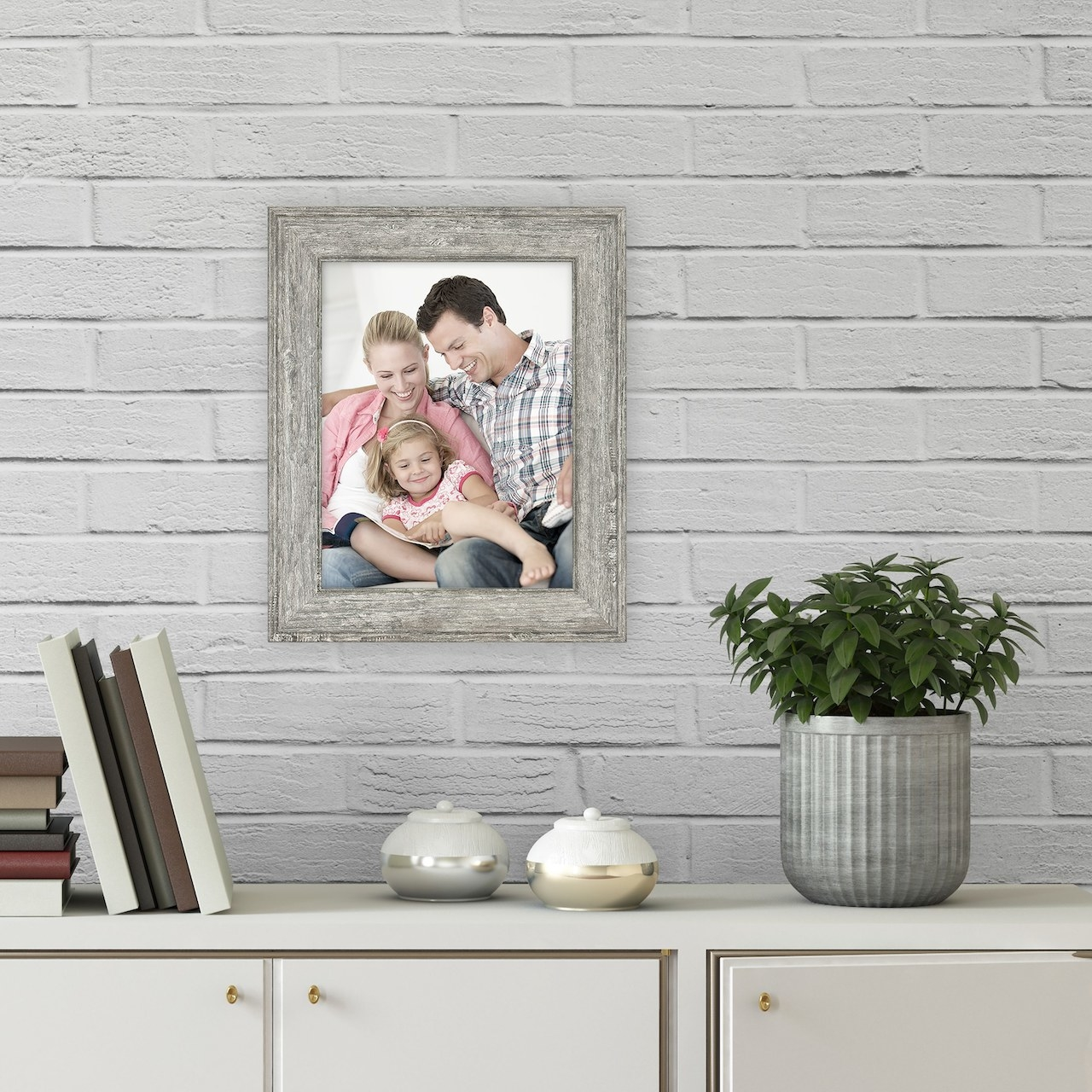 The frame hanging on a wall with a family photo inside