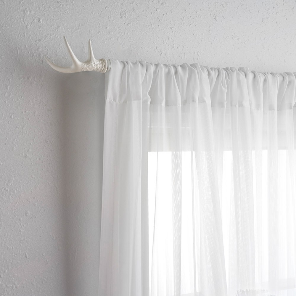 The white curtain rod with white curtains on it