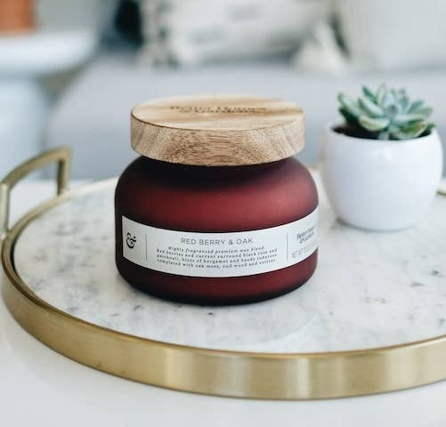 The candle in a red jar with a wood lid on a table