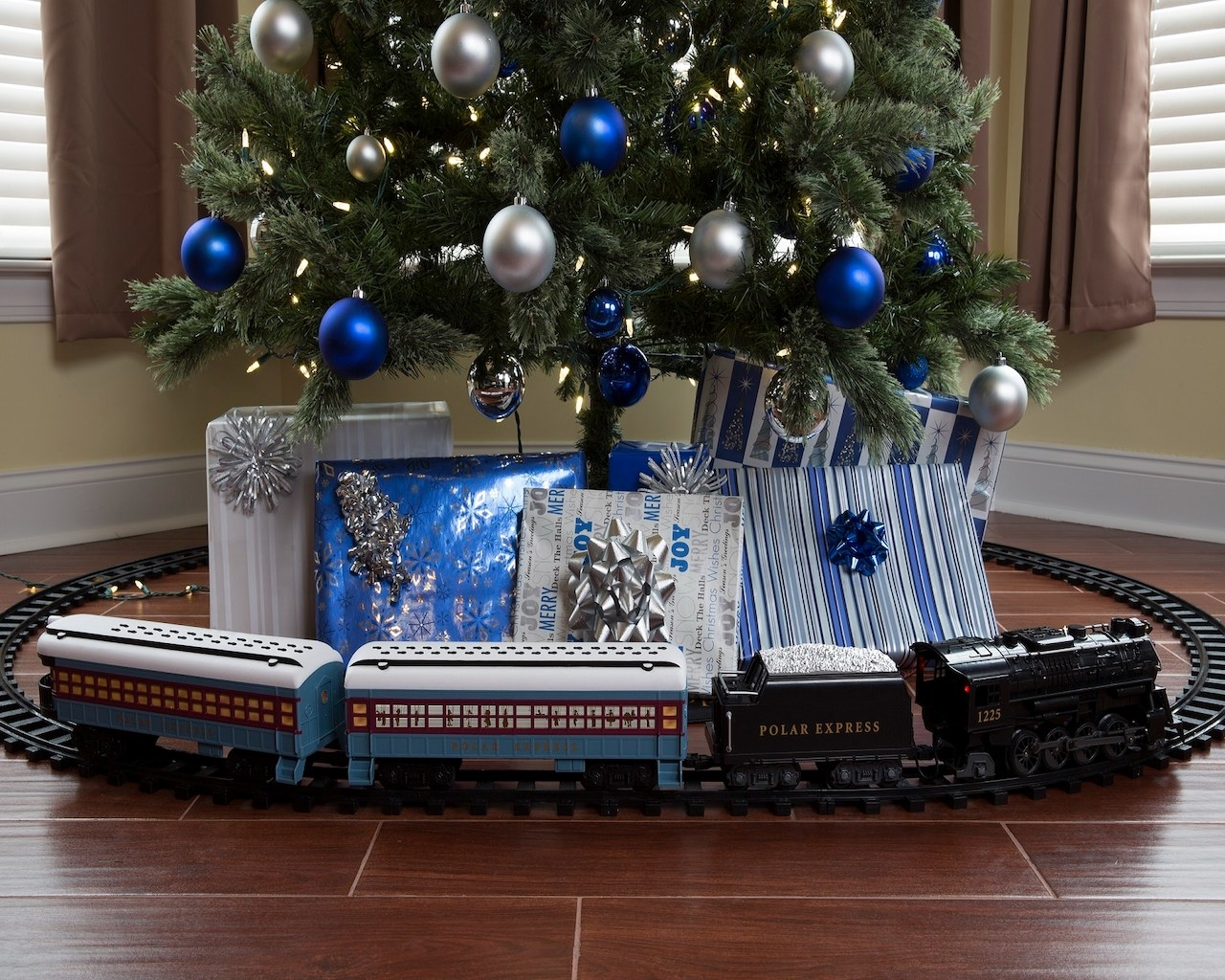 The train on its tracks going around the base of a Christmas tree