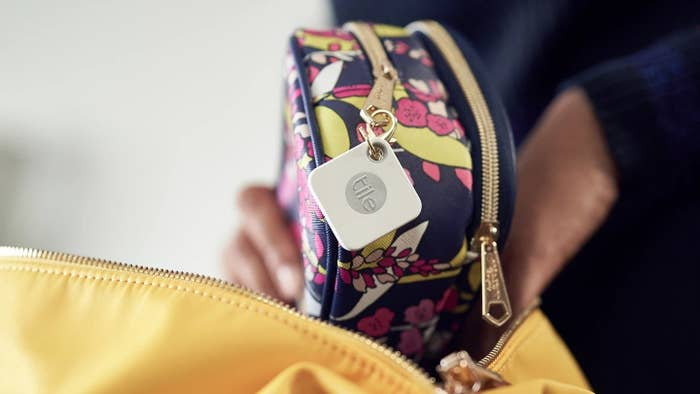 Hand holds makeup pouch with white Tile Mate tracker fasted onto a gold zipper