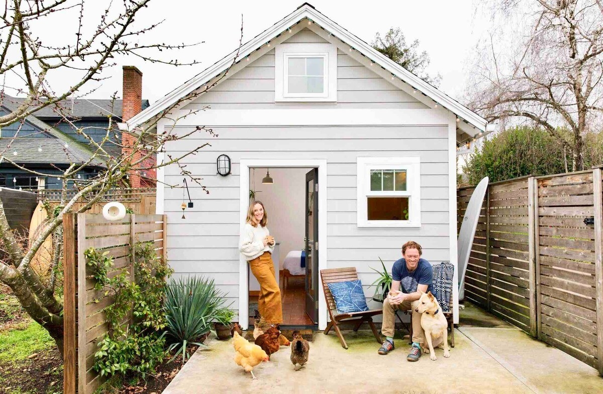 A couple sits outside a small white A-frame cottage with three chickens and a dog