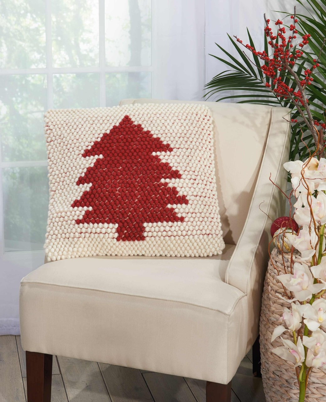 The ivory pillow, with a red Christmas tree on the front of it, resting on a chair
