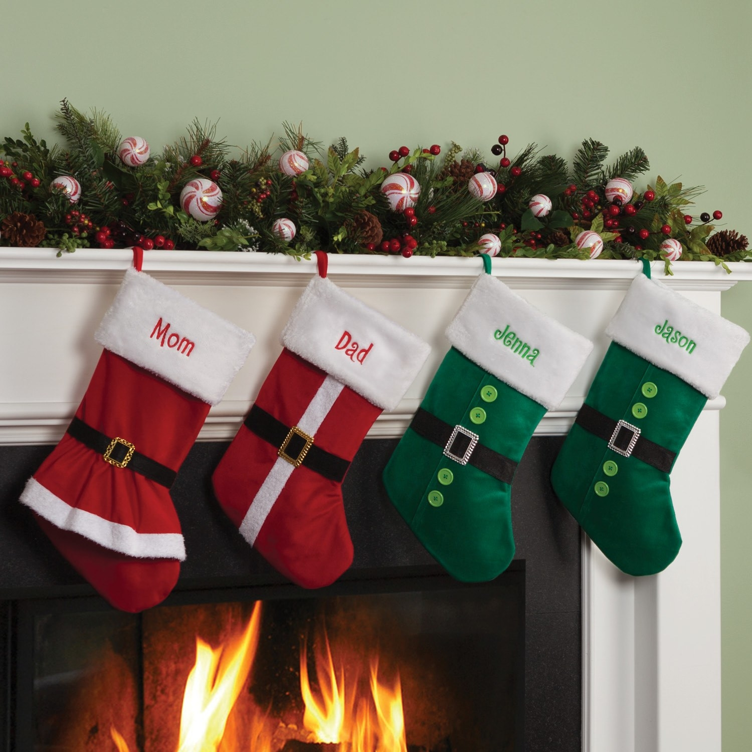 Four personalized stockings in different red and green styles above a fireplace